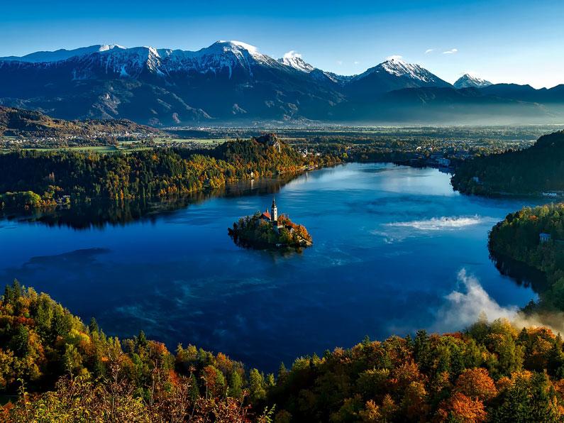 Um lago rodeado pelas montanhas com uma ilha no meio