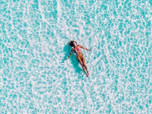 A mulher nadando no mar
