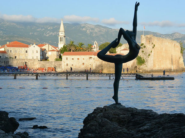 A statue of a woman with the city of Budva in the background