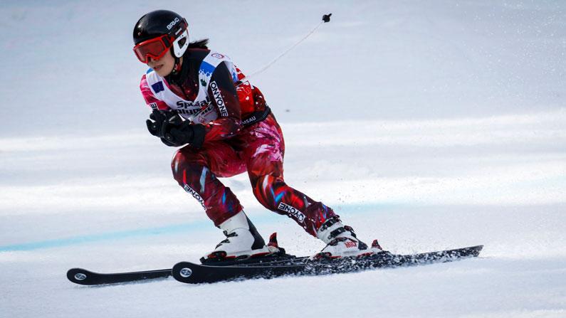 A mulher em esquis descendo a colina