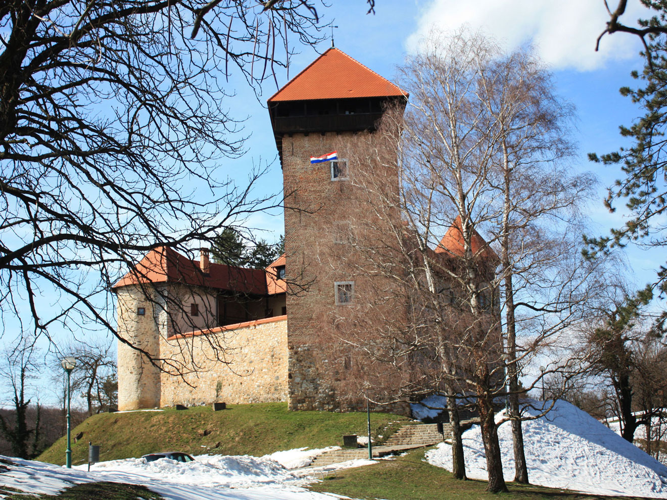 A medieval stone-built castle standing on a hill