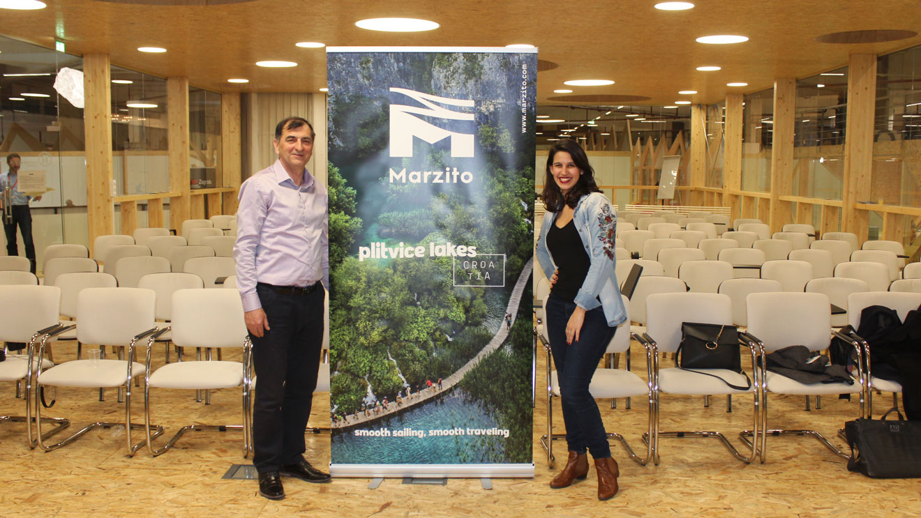 A photo of co-owners of Marzito Travel Agency standing next to the company logo