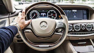 A hand on the steering wheel of the Mercedes