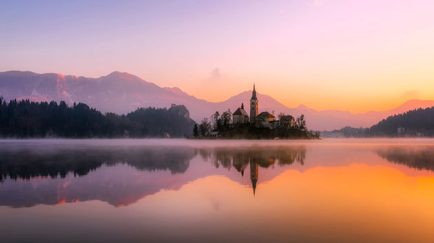 An island with a church in the middle of the lake in sunset