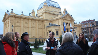 Local guide with a group of tourists in front of the National Theatre in Zagreb