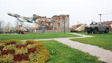 Um avião militar e um tanque no campo em frente à velha caserna arruinada