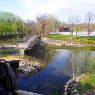 Uma ponte de madeira e um rio ao redor da caverna