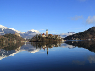 Lake Bled surrounded by the mountains with a church on an island in the middle of the lake