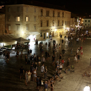 The town square full of people during the night