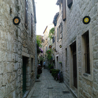 Narrow street paved in marble stones, with old stone houses