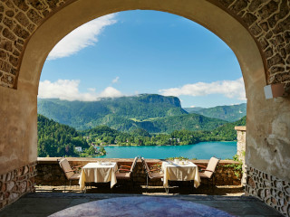 Two tables with chairs in the courtyard with a view at the lake