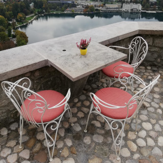 Three chairs and a table in the courtyard of the Bled Castle