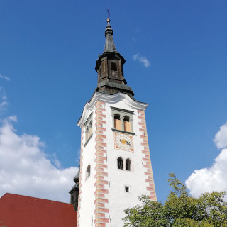 High bell-tower with a clock and a cross on the top