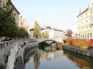 Rio Ljubljanica com Ponte Tripla e uma igreja no fundo