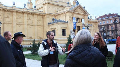 Local guide with a group of tourist in front of the national theatre in Zagreb