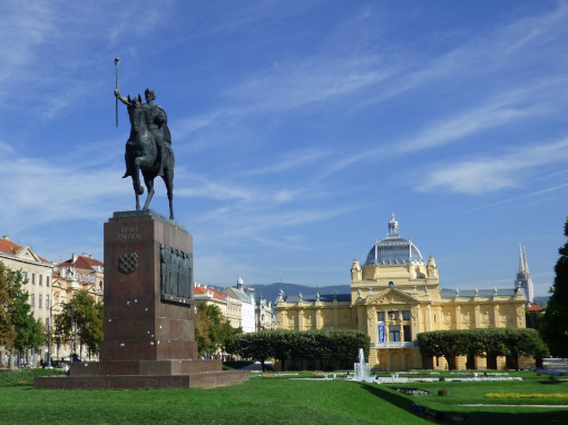 A statue of king on a horse with a park in the back