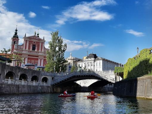 Dois barcos no rio com uma ponte de pedra no fundo