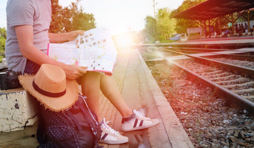 Homem sentado na estação com uma mapa nas mãos