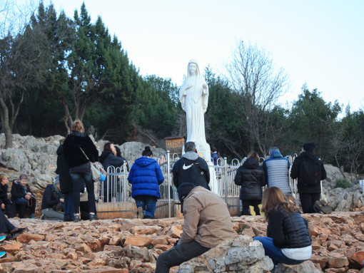 A statue of Virgin Mary with people praying around it