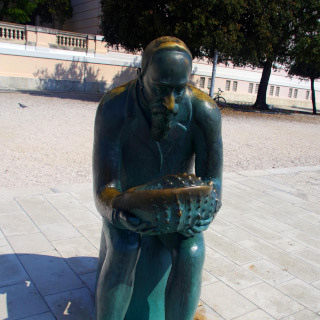 A statue of a man holding a shell