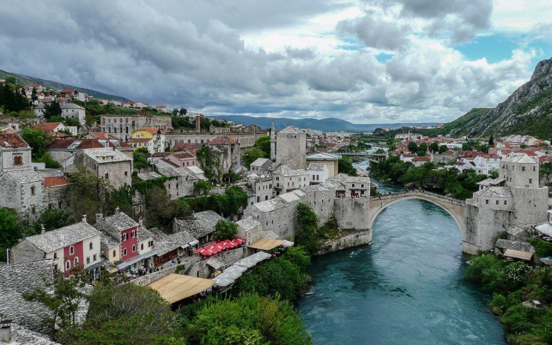 Vista da cidade com rio e uma ponte de pedra branca e casas antigas ao redor