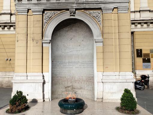 Um memorial com texto na parede e uma chama aberta em frente dela