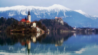 An island with a church in the middle of the lake with mountains in the background