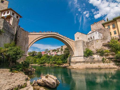 Ponte de pedra que atravessa o rio conectando casas de pedra