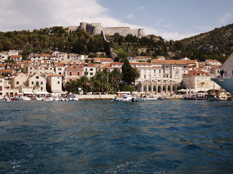 The city of Hvar port with a fortress on a hill in the background