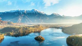 Un lago rodeado por el bosque y por las montañas, con una isla en el medio
