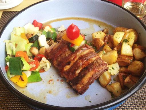 Costelas assadas com legumes, servidas em um prato