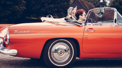 Two women driving in a red car