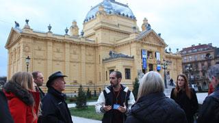 El guía local con un grupo de turistas enfrente del Teatro Nacional en Zagreb