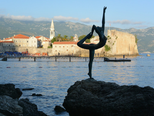 Statue of a dancer placed on a rock by the sea