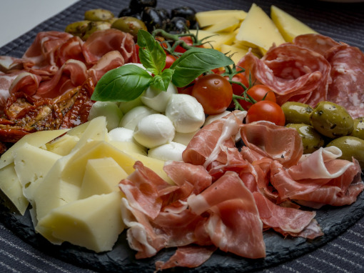 A plate with ham, olives, cheese, tomatos, etc.