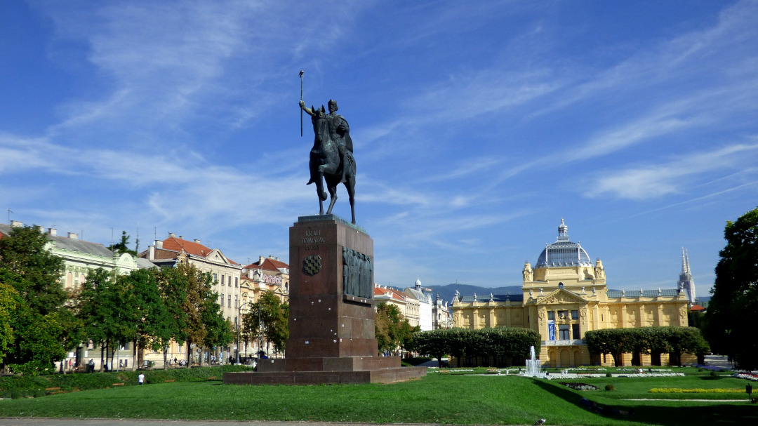 A statue of a man on horse with a park in the background