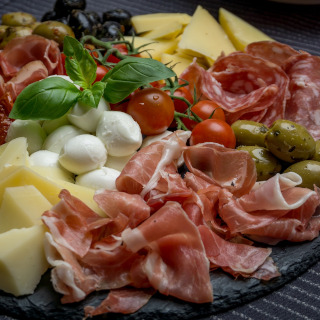 Plate with ham, cheese, olives, and other appetizers