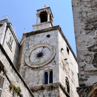 An ancient clock an a stone tower