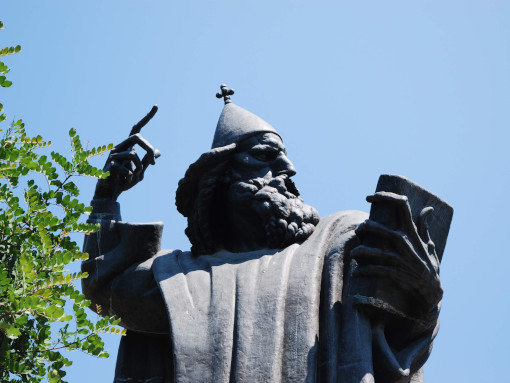Bronze statue of a man with bishop hat and a book
