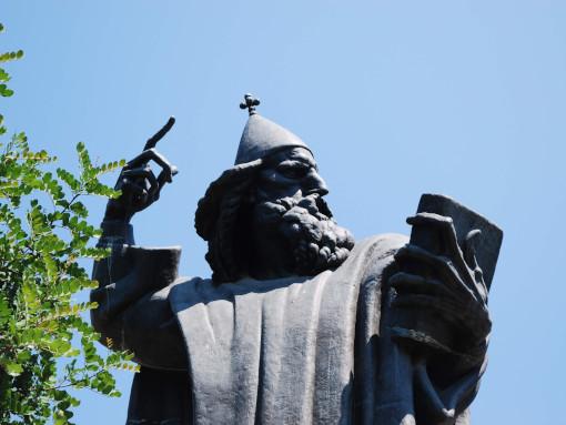 Estatua alta de bronze de homem com livro nos mãos e um chapéu do bispo