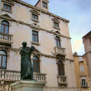Estátua de bronze do homem com livro