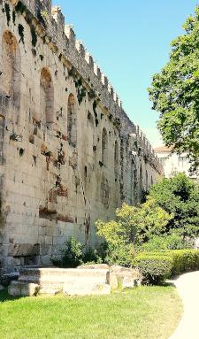 Uma alta muralha de pedra rodeada de árvores e parque