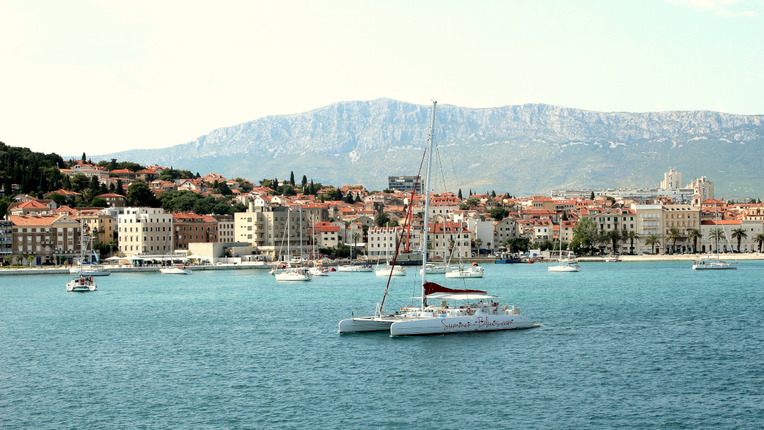 Sailing boat on the sea with the city of Split in the background