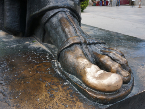 Close-up of a foot of the bronze man statue