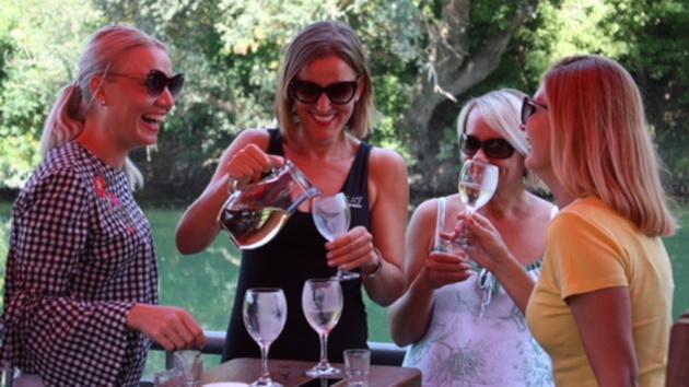 Cuatro mujeres beben vino y se ríen