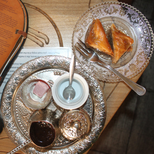 Metal tray with coffee pot and sugar next to the glass plate with a cake