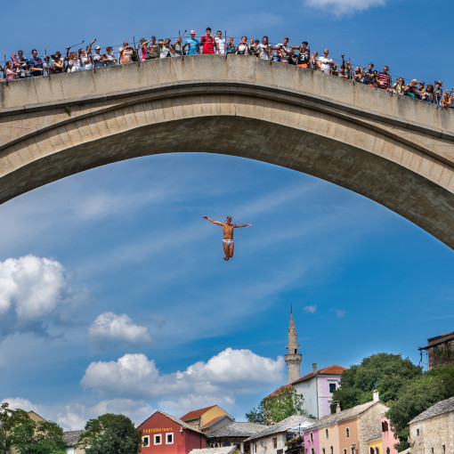 People lined up on a bridge, watching a man jump in the river
