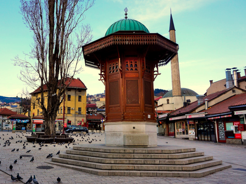 A wooden fountain in the middle of a square