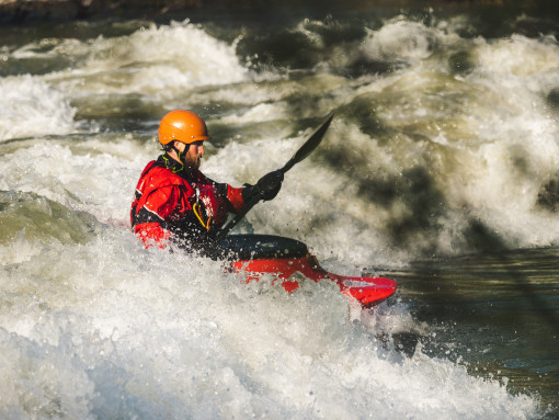 Man in a kayak sliding down the river rapids