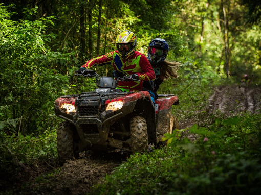 A man and a woman riding a quad through the forest